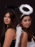 Good twin Bad Twin. Two identical twin sisters wearing white and black angel halos posing together over black stock photo