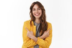 Always good two variants. Attractive relaxed smiling happy european girl pointing sideways hands crossed body show left stock image