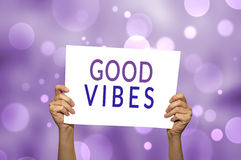 GOOD VIBES card in hand with abstract light background. Stock Images