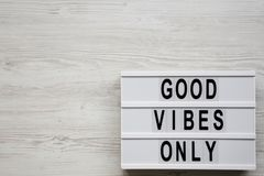 `Good vibes only` words on lightbox over white wooden background, top view. From above, overhead, flat lay. Copy space.  royalty free stock photography