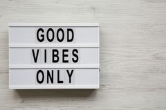 `Good vibes only` words on lightbox over white wooden surface, top view. From above, overhead, flat lay. Copy space.  royalty free stock photo