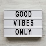 `Good vibes only` words on lightbox over white wooden surface, top view. From above, overhead, flat lay. Copy space.  royalty free stock photos