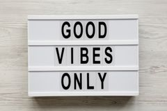 `Good vibes only` words on modern board over white wooden background, top view. From above, overhead, flat lay.  royalty free stock images