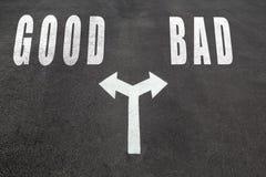 Good vs bad choice concept. Two direction arrows on asphalt Stock Photo