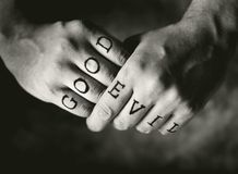 Good vs. Evil. Man with Good and Evil (fake) tattoos on his fingers royalty free stock image