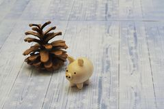 Good wooden pig and big pine cone on light background. Symbol of 2019. Handmade stock photography