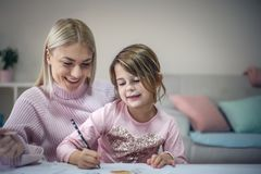 Good writing. Education at home. Preschool girl with mother having education at home. Close up royalty free stock image