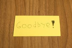 Goodbye handwrite on a yellow paper with a pen on a table Stock Photos