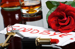 Goodbye Note. A goodbye note written with lipstick left by a woman near an open lipstick, red rose, keys and a glass of whiskey royalty free stock images