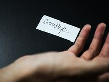 Goodbye note with man hand. On black background Stock Photo