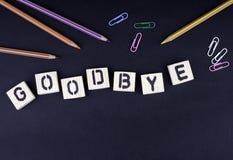 goodbye Simsen Sie von den hölzernen Buchstaben auf einem schwarzen Schreibtisch lizenzfreies stockfoto