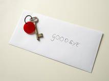 goodbye Wirklicher alter Schlüssel auf wirklichem Umschlag auf wirklicher Sahnefarbtabelle stockfotografie