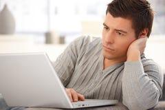Goodlooking man focusing on laptop. Portrait of goodlooking man focusing on laptop computer screen, typing on keyboard, looking serious stock image