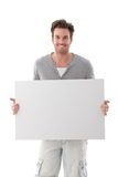 Goodlooking man holding white panel smiling. Goodlooking young man holding a blank sheet, smiling Stock Photo
