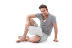 Goodlooking man using laptop smiling Stock Images