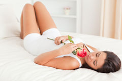 Goodlooking woman with rose lying on bed Royalty Free Stock Images