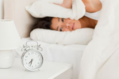 Goodlooking woman waking not wanting to hear alarm. Goodlooking woman waking under sheet not wanting to hear alarm clock in bedroom royalty free stock photo
