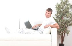 Goodlooking young man relaxing at home sitting in living room stock images