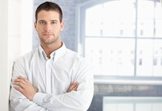 Goodlooking young man standing arms crossed Stock Photo