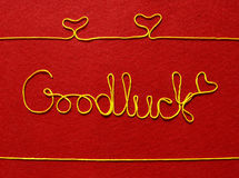 Goodluck ribbon greeting and hearts on red background Royalty Free Stock Photo