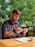 Goodly молодой человек работая на таблетке пока сидящ outdoors владение домашнего ключа принципиальной схемы дела золотистое дост Стоковое фото RF