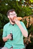 Goodly boy with a glasess tasting delicious food in the park. Nature background. Royalty Free Stock Photography