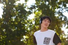 Goodly jongen met een zwarte oortelefoon op een groene achtergrond van bomen stock fotografie
