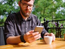 Goodly young man working on tablet while sitting outdoors . Business concept. royalty free stock images