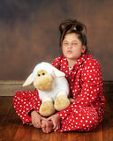 Goodnight Kiss. A cute preteen girl in poka-dot pajamas puckered up for a good-night kiss.  She's holding a cute plush lamb Stock Photography