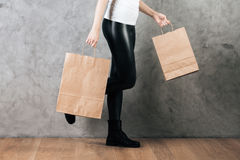 Goods concept. Close up of woman holding empty craft paper bags for shopping on concrete wall background. Goods concept. Mock up Royalty Free Stock Photography