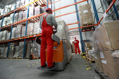 Goods delivery in storehouse. Goods delivery - two workers working in storehouse with forklift loader Royalty Free Stock Photography