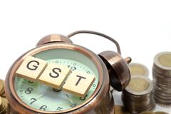 Goods and Services Tax word on Alarm clock and stacks coins Stock Photos