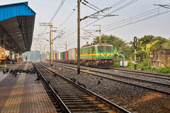 Goods train passes a deserted Indian railway station. Royalty Free Stock Photos