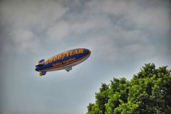 Goodyear blimp flying in cloudy sky stock image