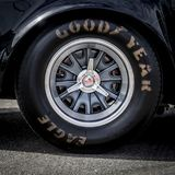 Goodyear racing tire on a vintage sports car. A Goodyear racing tire and wheel mounted on a vintage sports car Stock Photo