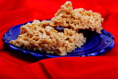 Gooey Rice Crispy Treats. Yummy gooey rice crispy treats on a pretty blue plate and bright red cloth. Shallow depth of field Stock Photography