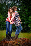 Goofball BFF Girls. Two pretty young goofball country girls with long hair playing outdoors. Trees in background. Shallow depth of field Royalty Free Stock Images