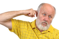 Goofy bald senior mans picking his ear. Goofy bald senior man picking his ear with index finger Stock Image