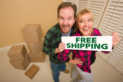 Goofy Couple Holding Free Shipping Sign Near Boxes Stock Image