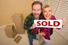 Goofy Couple Holding Sold Sign Surrounded by Boxes Royalty Free Stock Images
