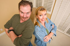 Goofy Couple and Moving Boxes in Empty Room Royalty Free Stock Photos