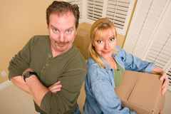 Goofy Couple and Moving Boxes in Empty Room Stock Photo