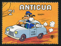 Goofy driving taxi. ANTIGUA - CIRCA 1980: stamp printed by Antigua, shows Disney Characters, Goofy driving taxi, circa 1980 Stock Photography