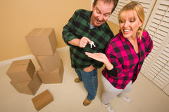 Goofy Excited Man Handing Keys to Smiling Wife. In Room with Packed Boxes Royalty Free Stock Image