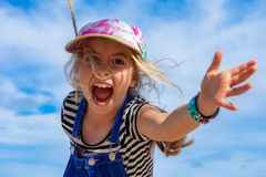 Goofy Girl Swings through the Air. A sweet and goofy little girl swings through the air on a rope royalty free stock photography