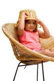 Goofy Kid. A young girl sitting in a wicker chair, isolated against a white background Stock Photos