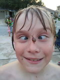 Goofy kid looking cross-eyed at a snail on his nose Royalty Free Stock Photos