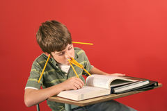 Goofy kid studying with pencil. Shot of a goofy kid studying with pencils Stock Photo