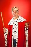 Goofy King. Senior man in king`s dress, making faces royalty free stock photography