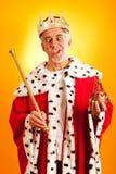 Goofy King. Senior man in king`s dress, making faces royalty free stock images